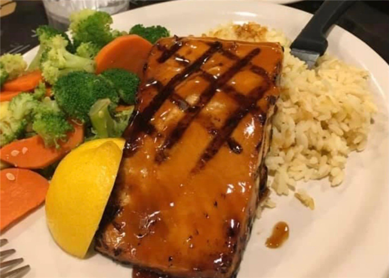 Grilled salmon topped with sauce with a side of rice and cooked vegetables