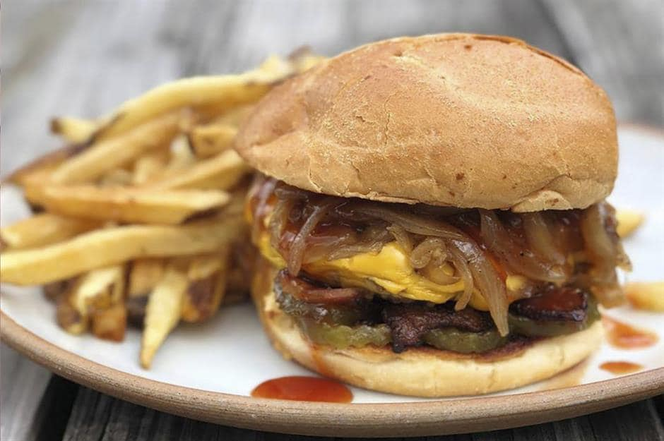 cheeseburger with sauteed onions and pickles. french fries on the side