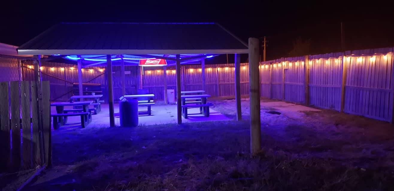 outside patio area with tables and neon lights at night