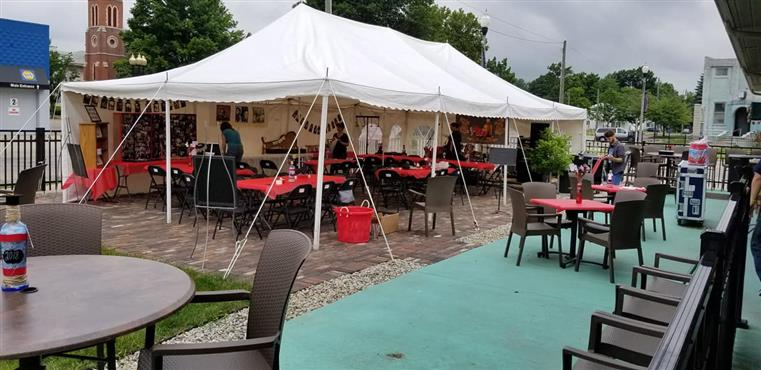 outside patio with tables and a tent setup for a party