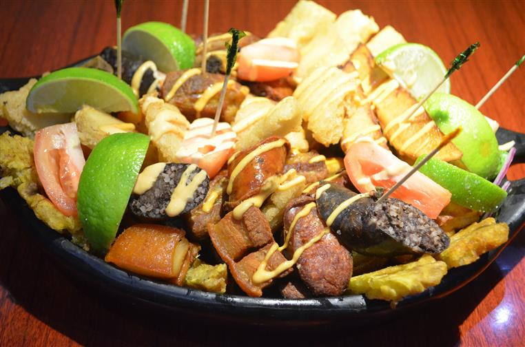 Picada for 2: A mix of fried pork sausage, black sausage, pork ribs, pork belly, yuca, green plantains, yellow potatoes, potato wedges, grilled chicken breast, & grilled Palomilla steak.