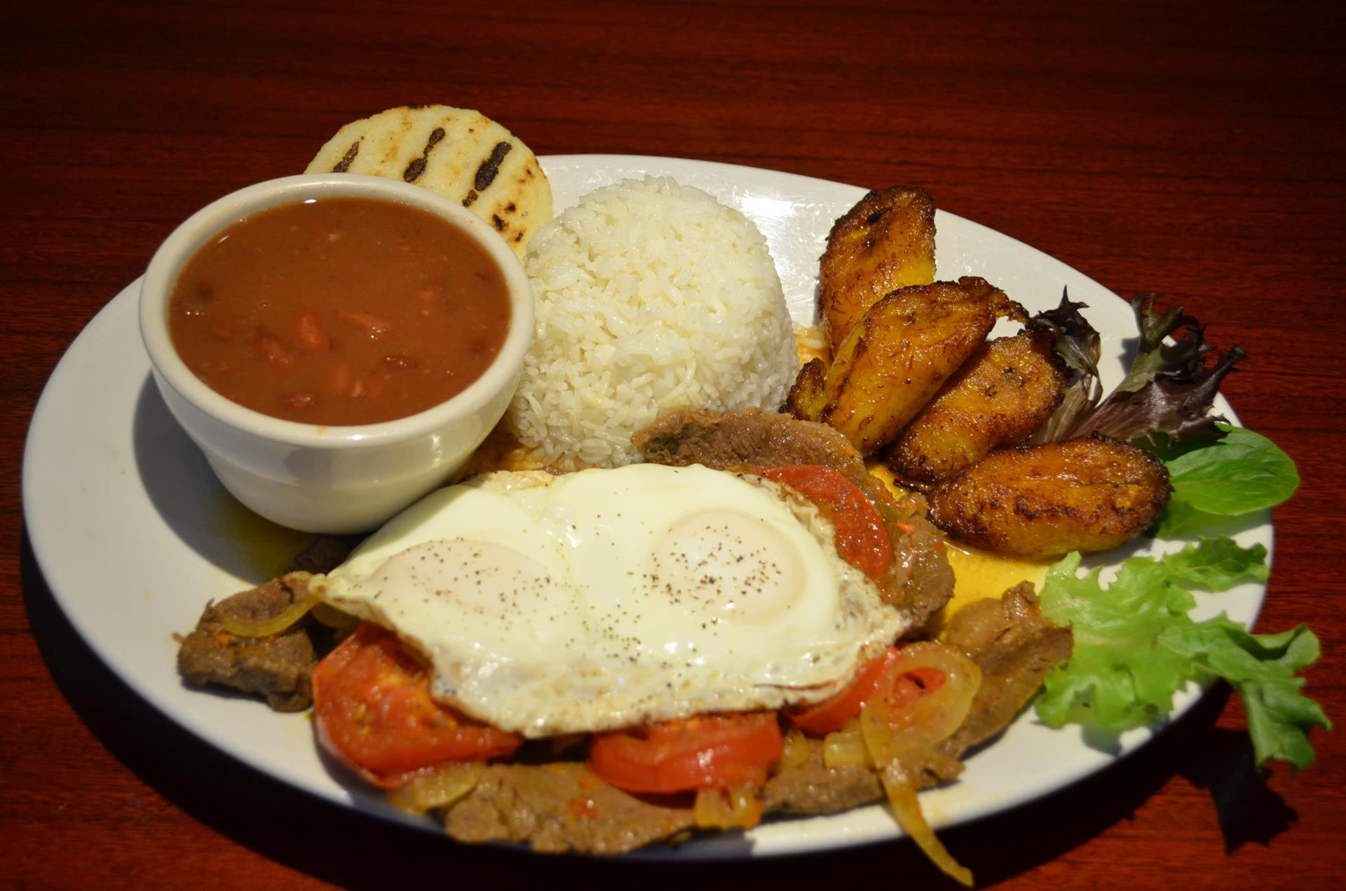 Calentado Valluno: Grilled steak, two eggs, mixed rice & lentils with diced sweet plantains and a small arepa