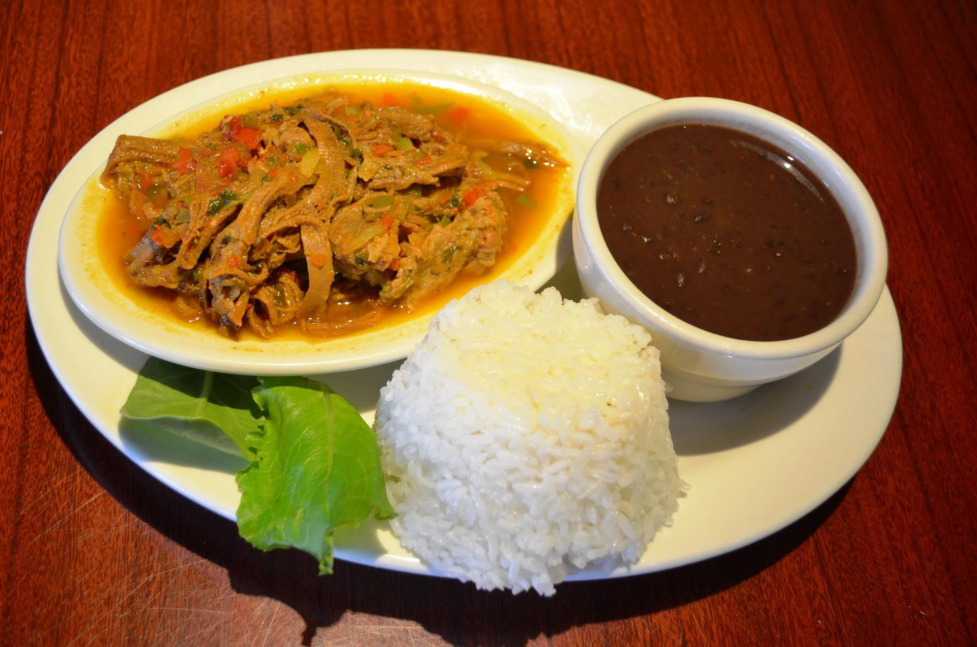 Frijolada: Red beans with shredded beef, pork belly, sweet plantains, corn & avocado. Served with white rice, arepa, & creole sauce.