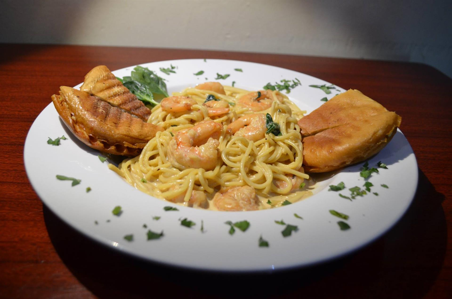 Pasta Con Camarones: Angel hair pasta sautéed in a white, creamy garlic sauce with spinach and tomatoes.