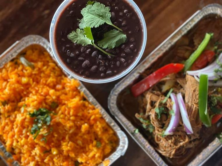 trays of pulled chicken, seasoned rice, and black beans