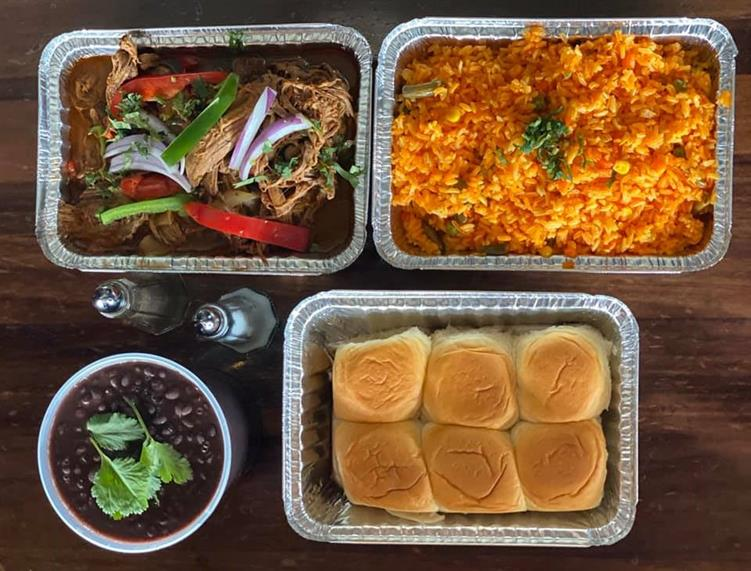 trays of pulled chicken, bread, seasoned rice, and black beans