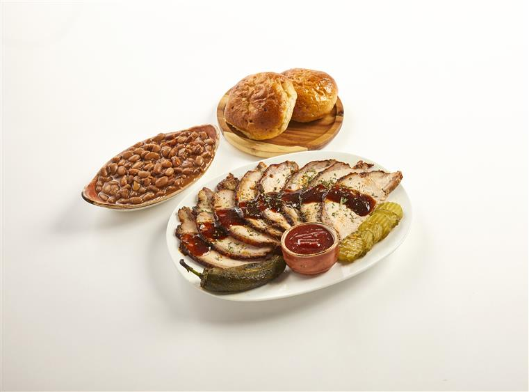 sliced, roasted turkey with a bowl of baked beans and a plate of dinner rolls