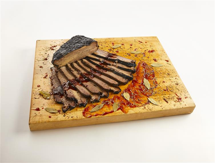 brisket on a cutting board sliced and topped with BBQ sauce, herbs and bay leaves