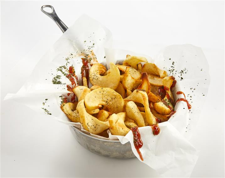 curly french fries in a basket with ketchup