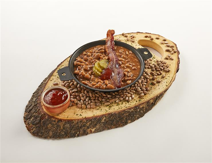 bowl of baked beans with bacon and pickles