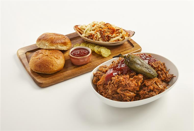 bowl of pulled pork with dinner rolls, sauce, pickles, and coleslaw