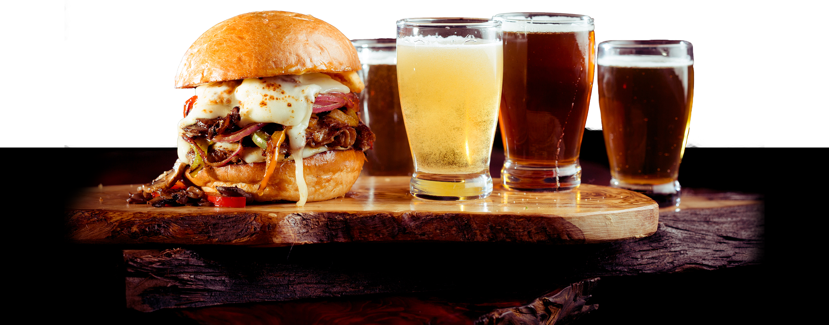 burger with melted cheese and assorted glasses of beer