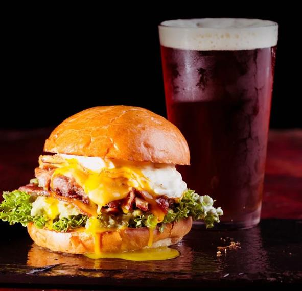 Savage Burger: Smoked bacon, over easy egg, American cheese, guacamole, jalapeño onion hash, leaf lettuce, garlic aioli