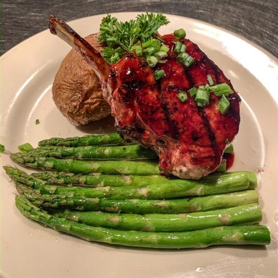 pork chop with asparagus and a baked potato