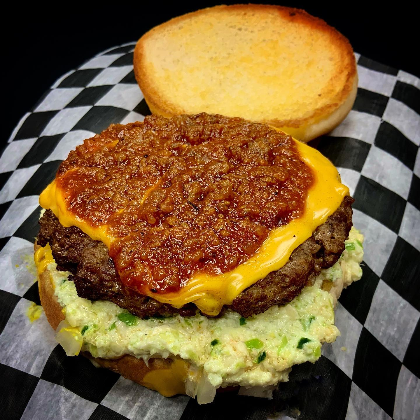 cheeseburger with lettuce topped with chili