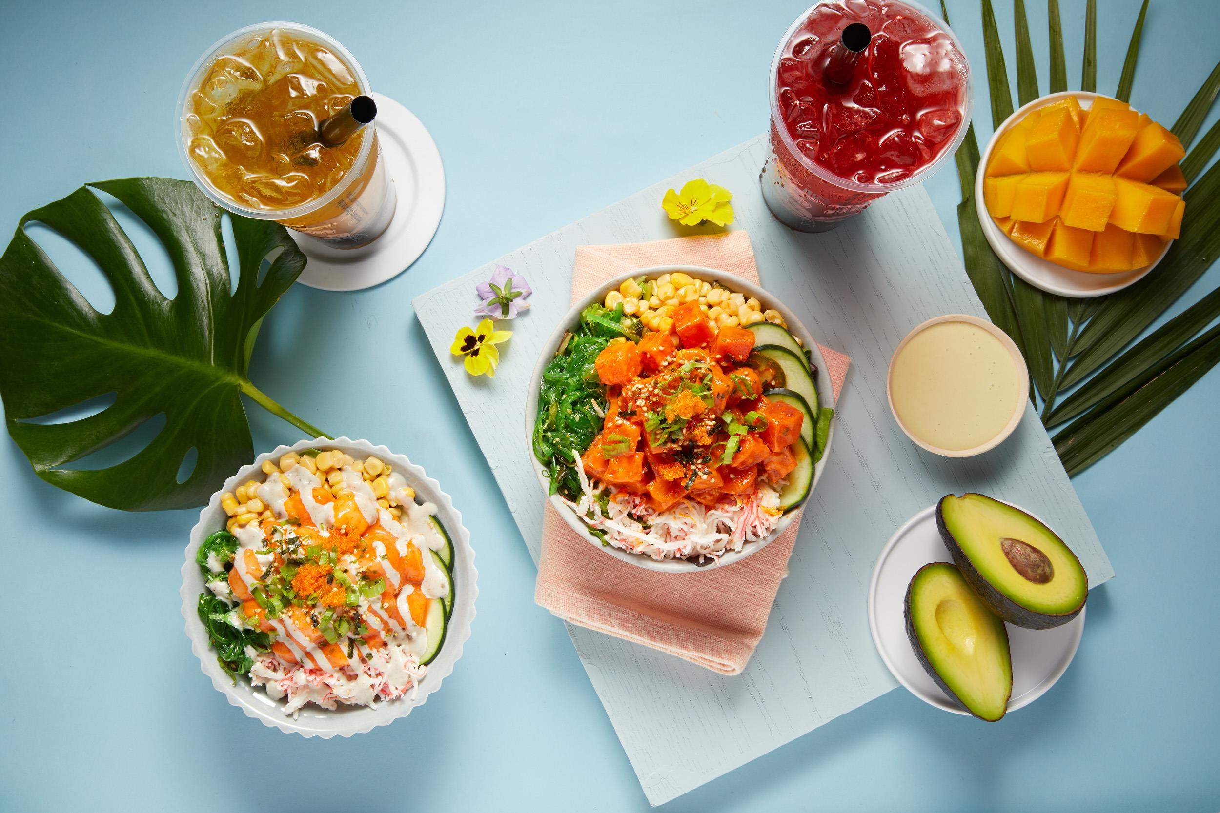 Looking down at a spicy tuna poke bowl, spicy scallop poke bowl, two drinks, a mango, avocado and two large tropical leaves