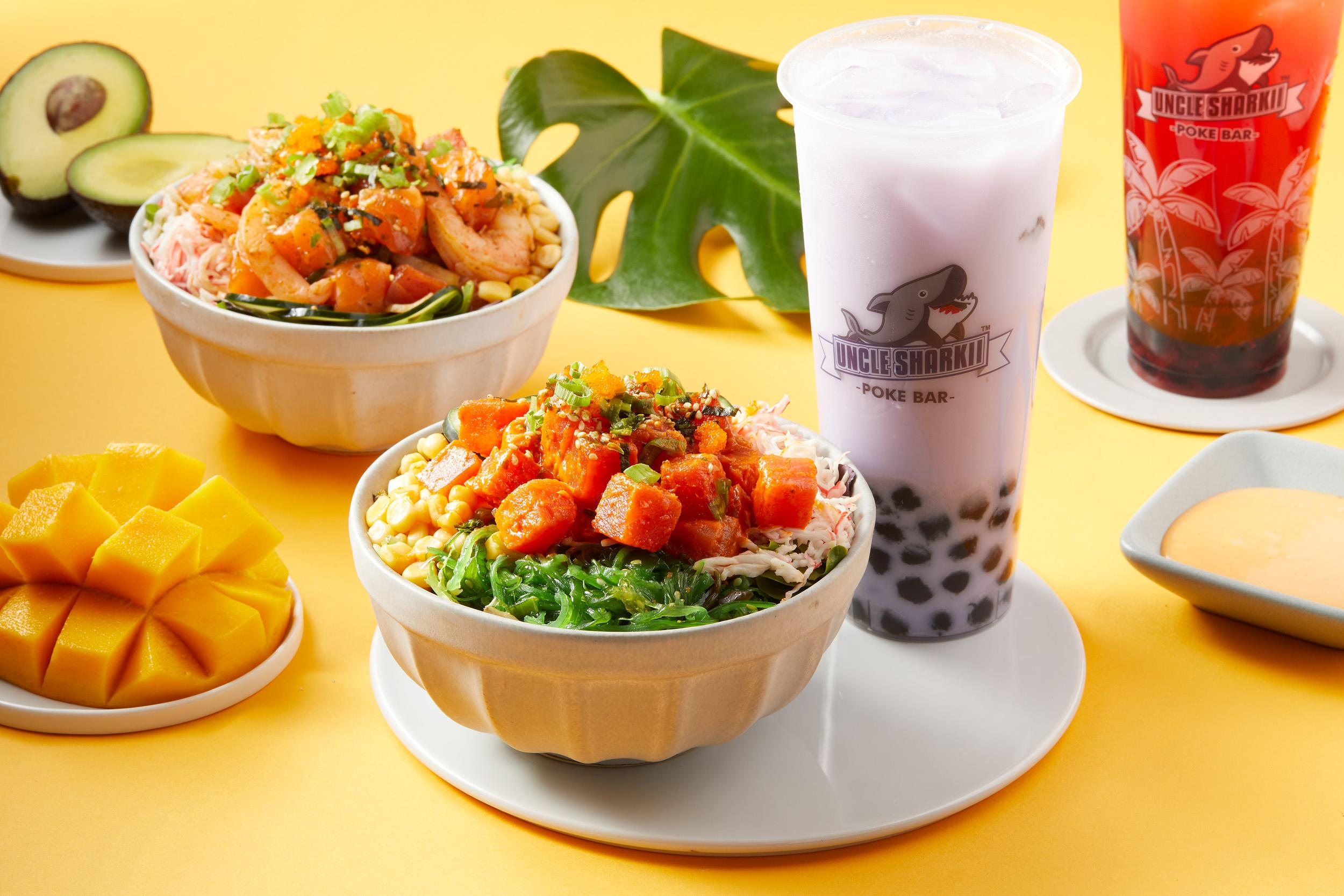 Two bowls of poke with a drink, mango, avocado and a tropical leaf