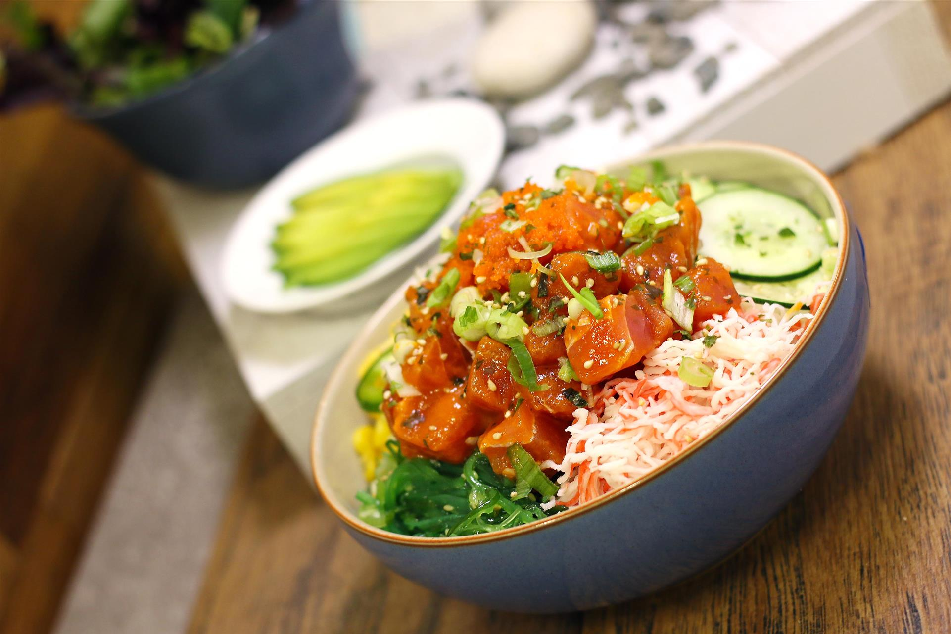 poke bowl with various ingredients, alongside side plate of sliced avocados