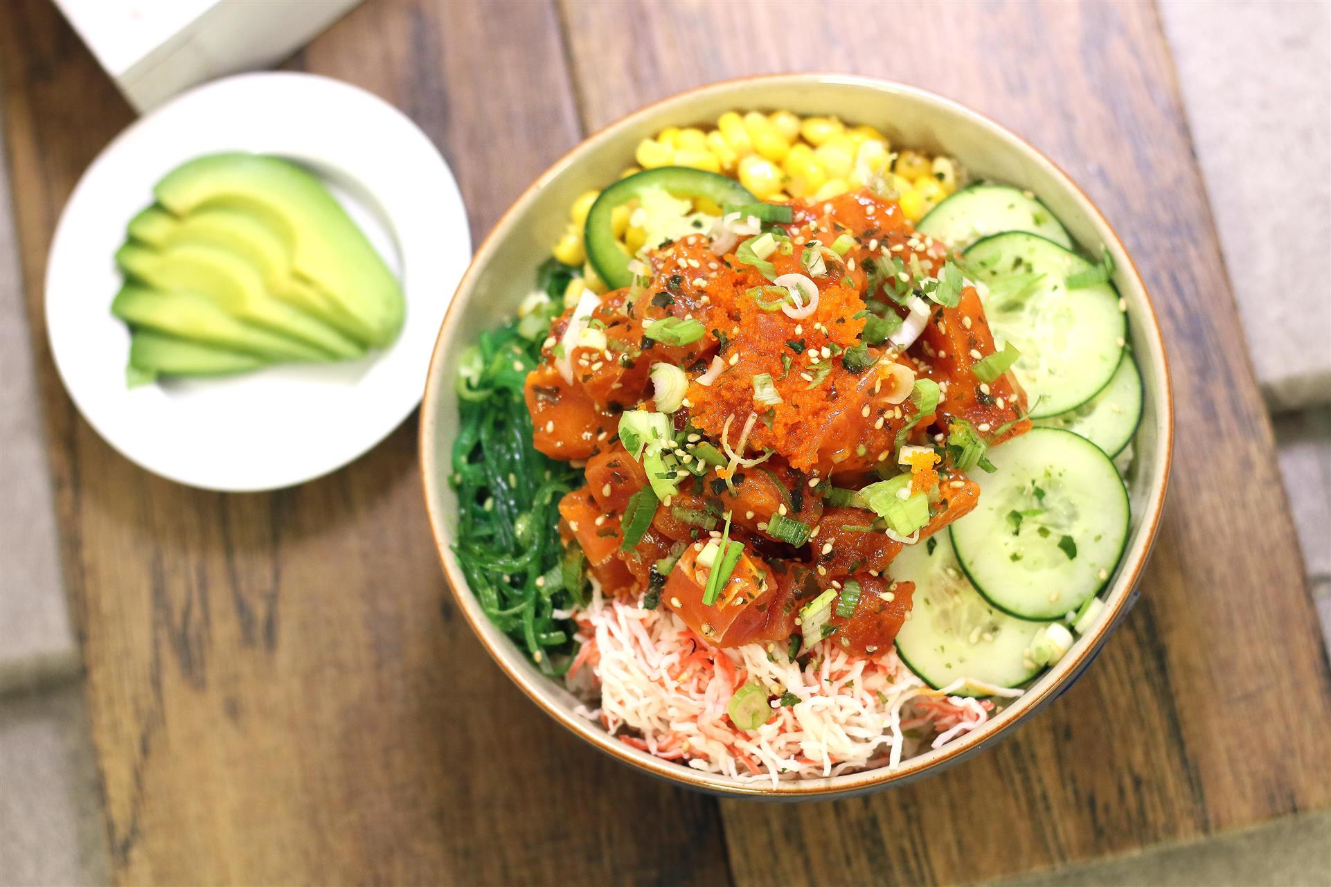 poke bowl with various ingredients, including cucumber slices and corn, with side plate of avocados