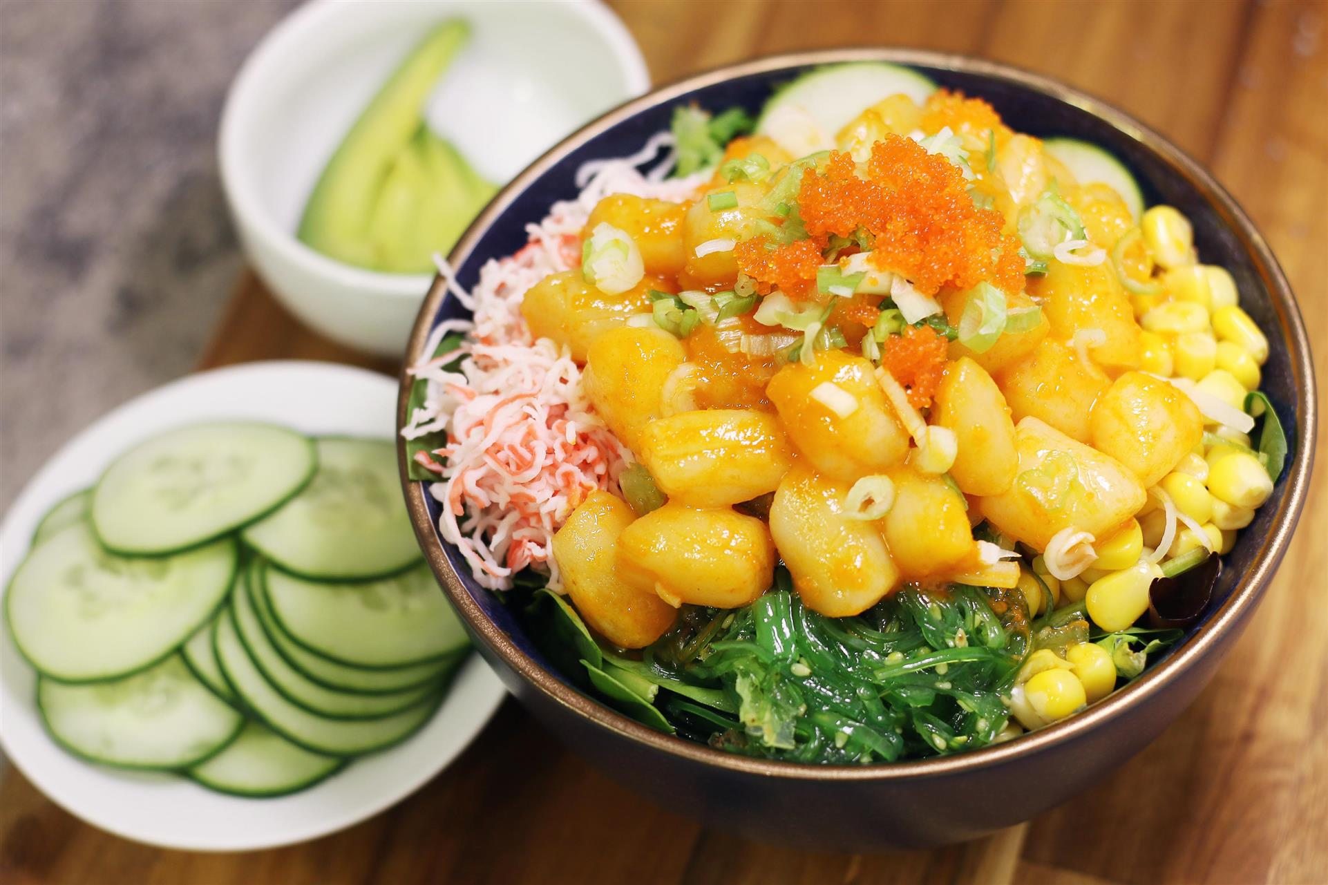 vegetable poke bowl with side plates of sliced cucumbers and sliced avocados