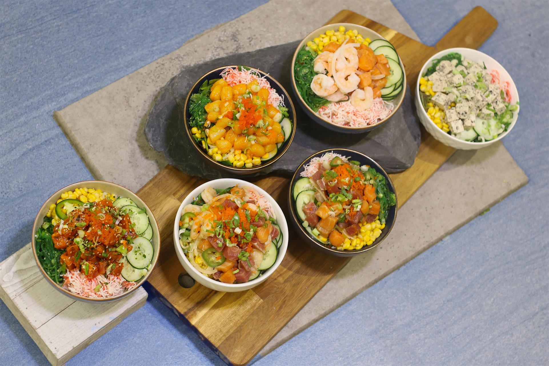 six poke bowls, all with various ingredients