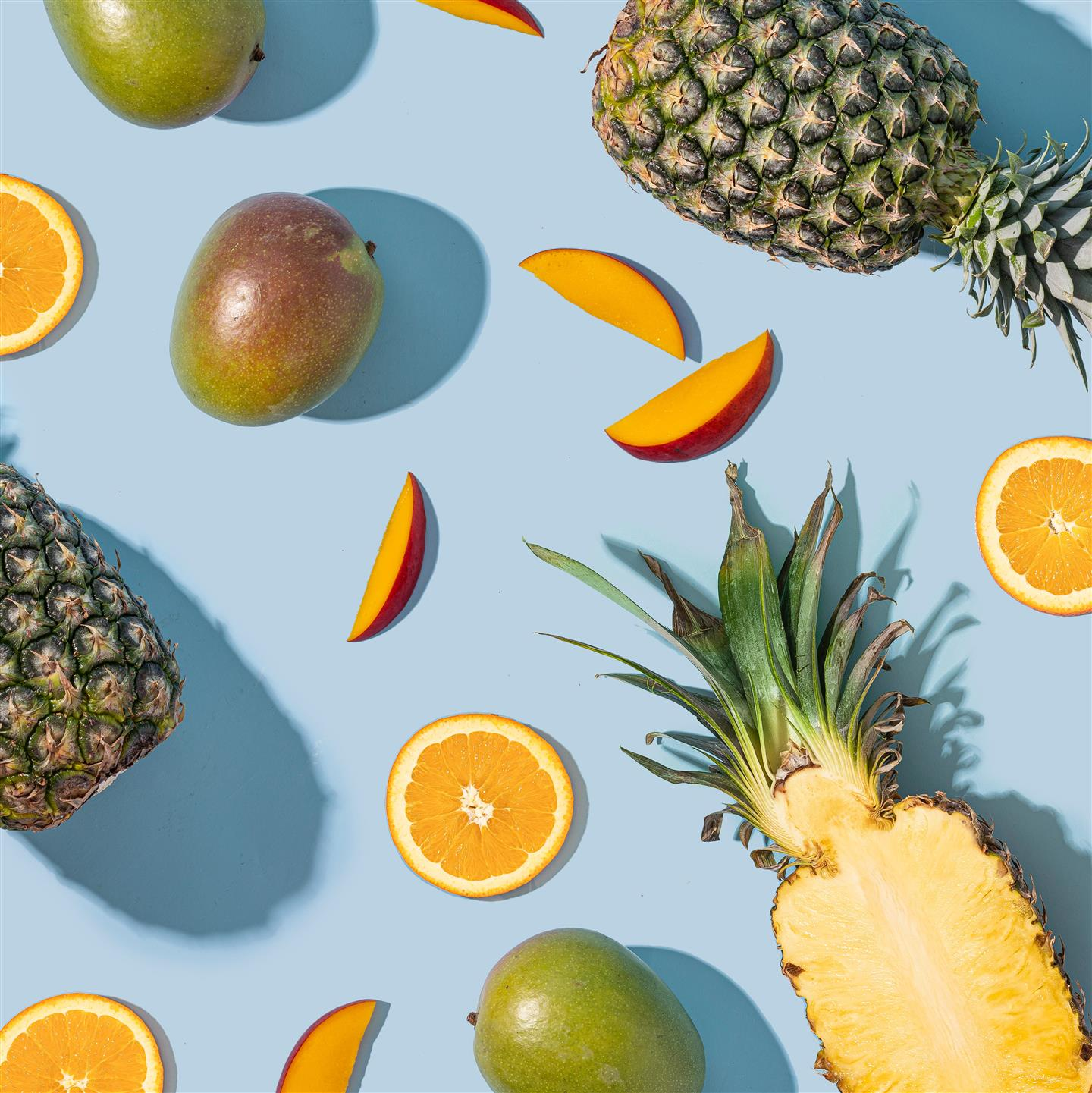 cut up mangos/oranges and pineapple background