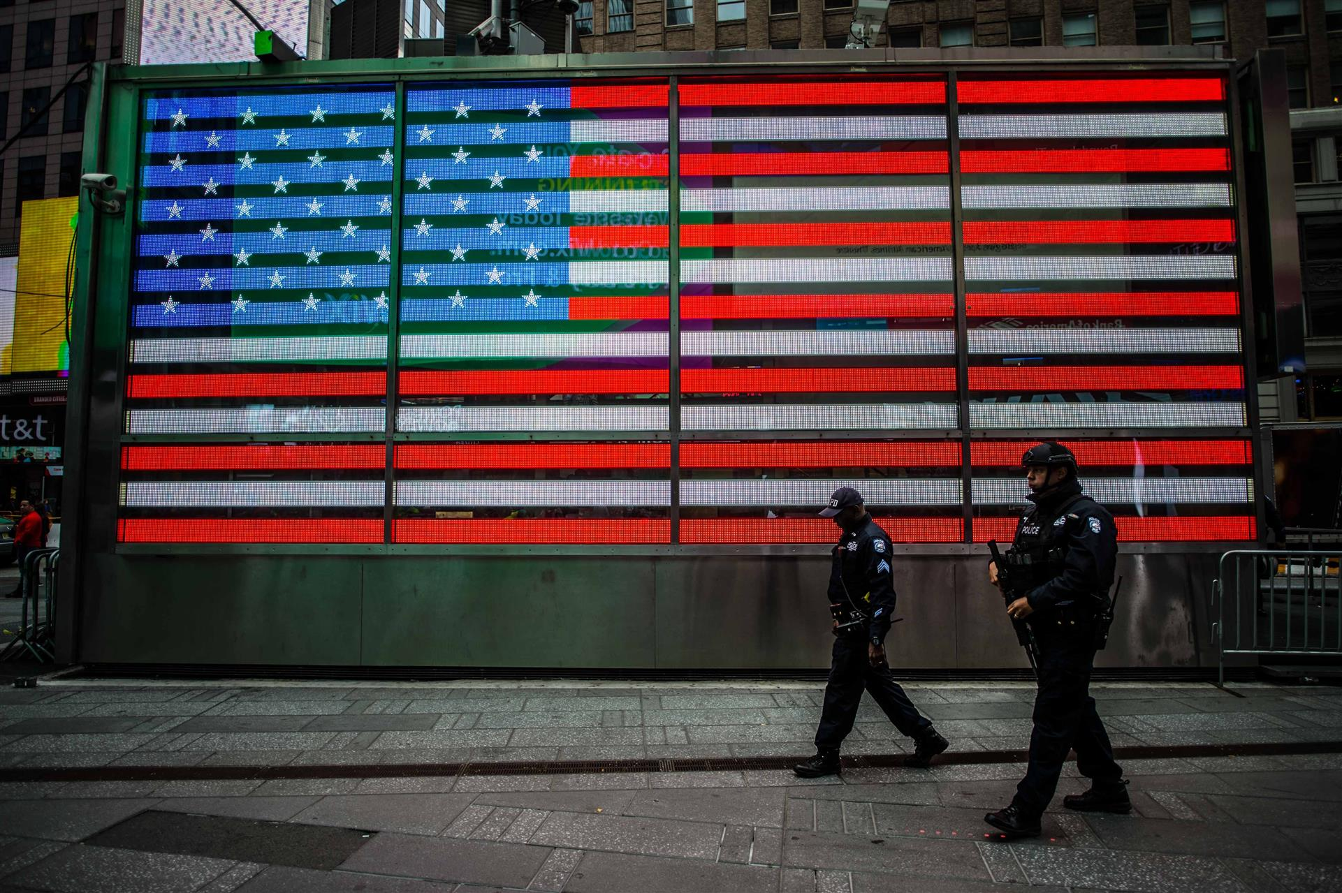 two police walking in front of an American Flag