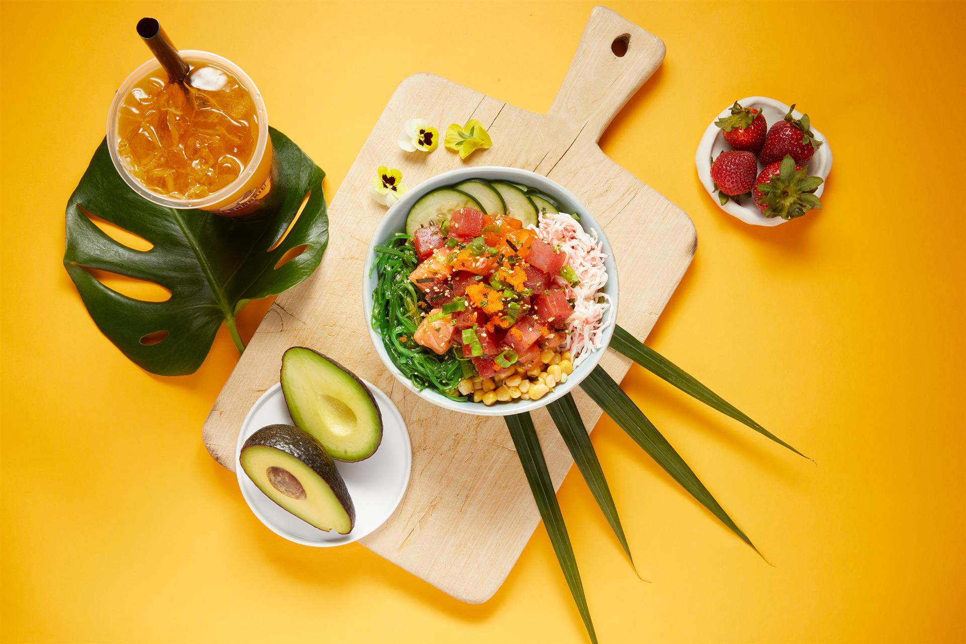 poke bowl on a tray with avocado on the side and a drink