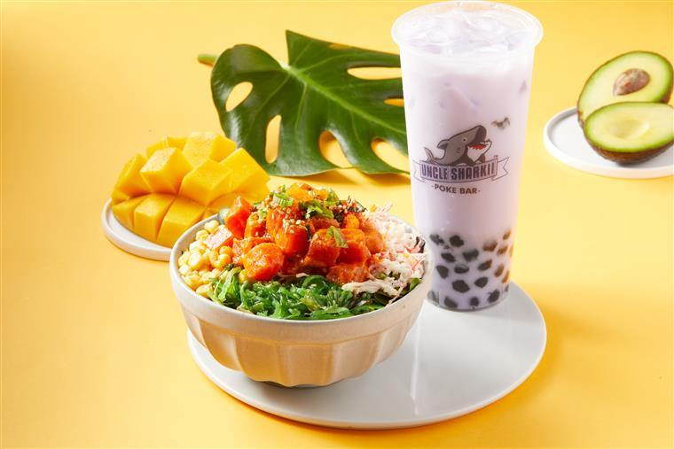 spicy tuna poke bowl with a taro drink. in the background there is a cut mango, a leaf, and an avocado