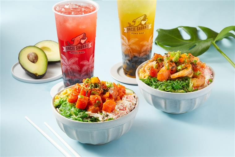 Two poke bowls with two drinks on a table with an avocado cut in half behind