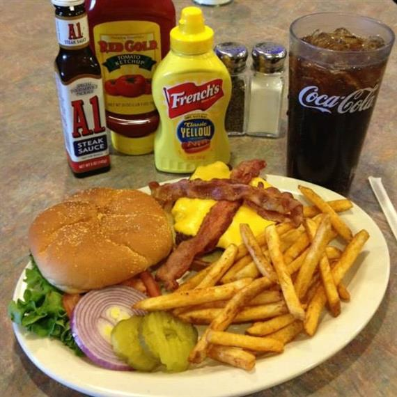 bacon cheeseburger with lettuce, tomato, red onion and pickles with a soda and fries on the side