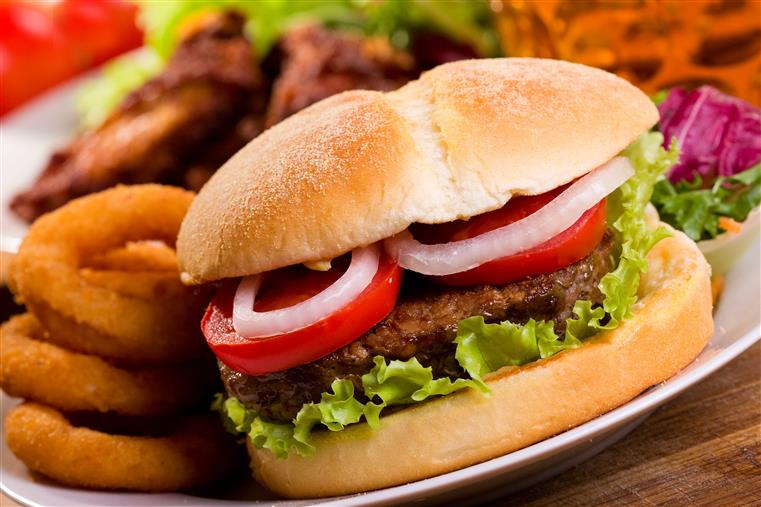 burger with onion rings and a salad