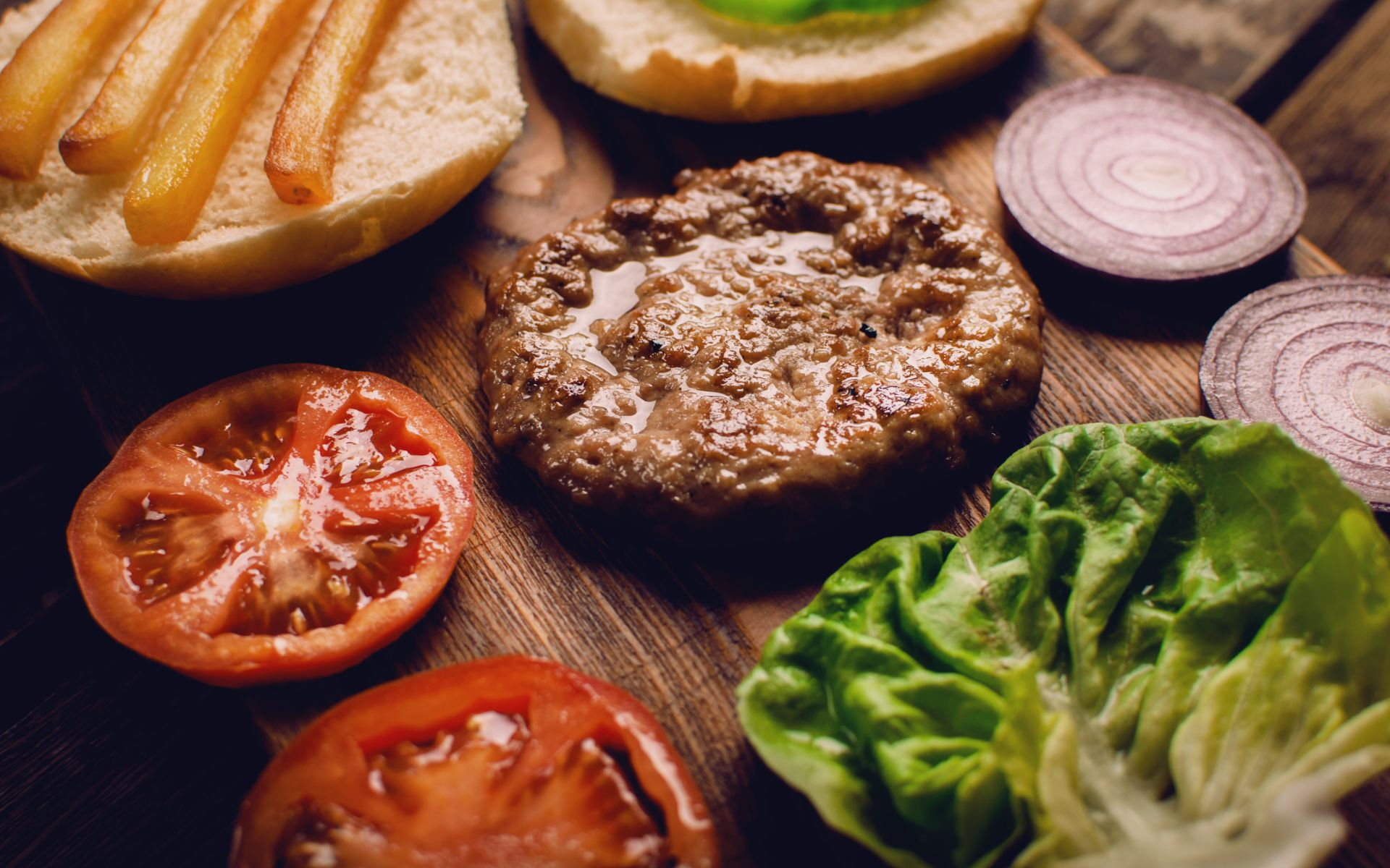 burger with tomato, lettuce and bun on wood