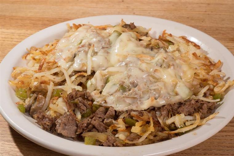 breakfast skillet with steak, hashbrowns, peppers, onions, topped with melted cheese