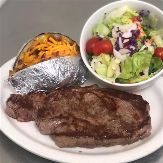 Steak with a side salad and loaded baked potato