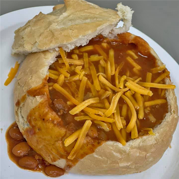 Chili in a bread bowl topped with cheese