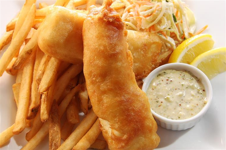 fish and chips with sides of tartar sauce and coleslaw