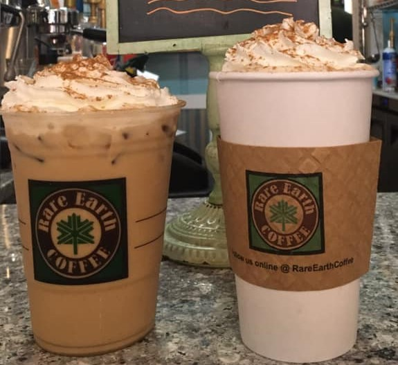 one hot and one cold coffee each topped with whipped cream