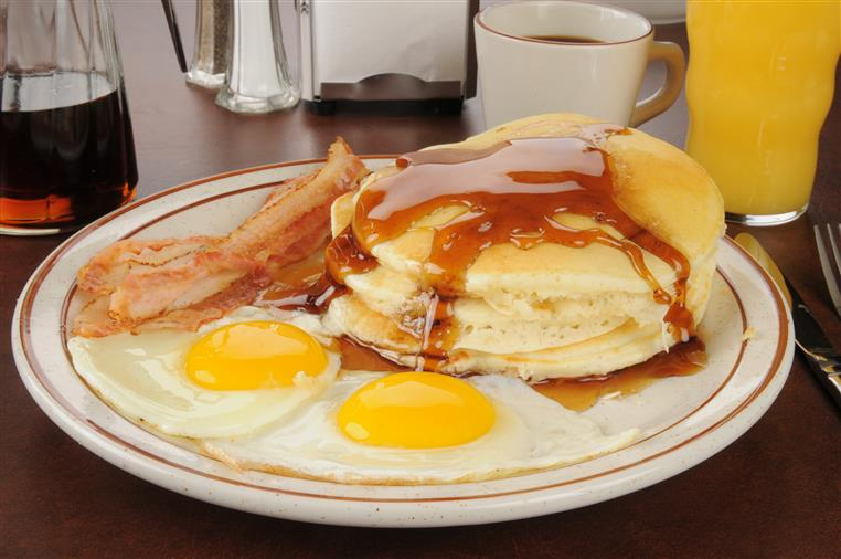 stack of pancakes with maple syrup and bacon and eggs on the side