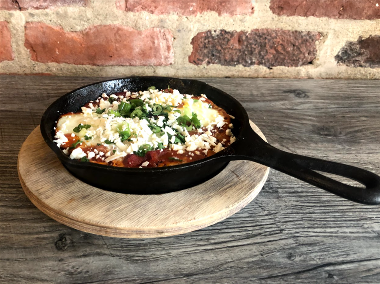 shashuka in a skillet topped with queso fresco