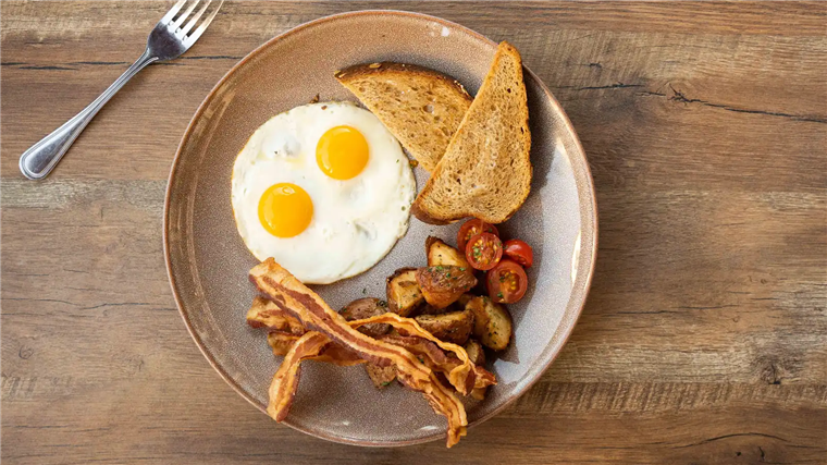 eggs over easy, bacon, potatoes, tomatoes, and toast on a plate with a fork