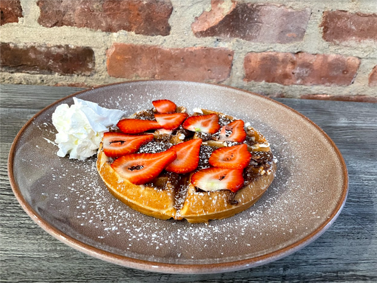 waffle made in heaven: waffle topped with nutella and sliced strawberries