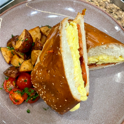 breakfast sandwich with eggs and bacon on a plate with potatoes and tomatoes