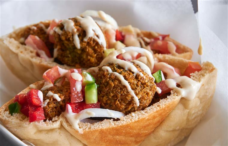 falafel in a pita with tomato, cucumber and onion