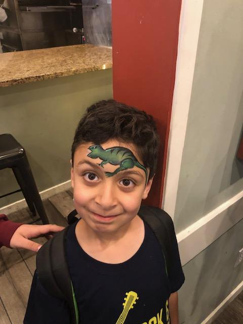 child with face painting of a dinosaur