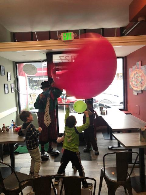 children playing with a clown and balloons