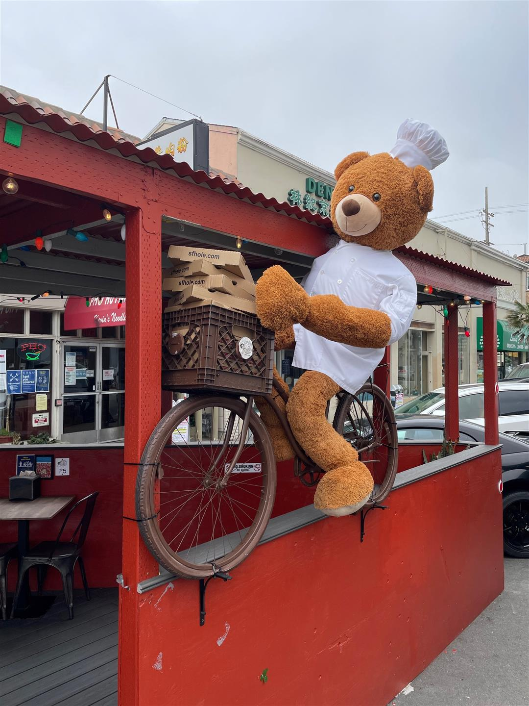 Chef stuffed Bear on a bike holding pizza boxes in front of restaurant
