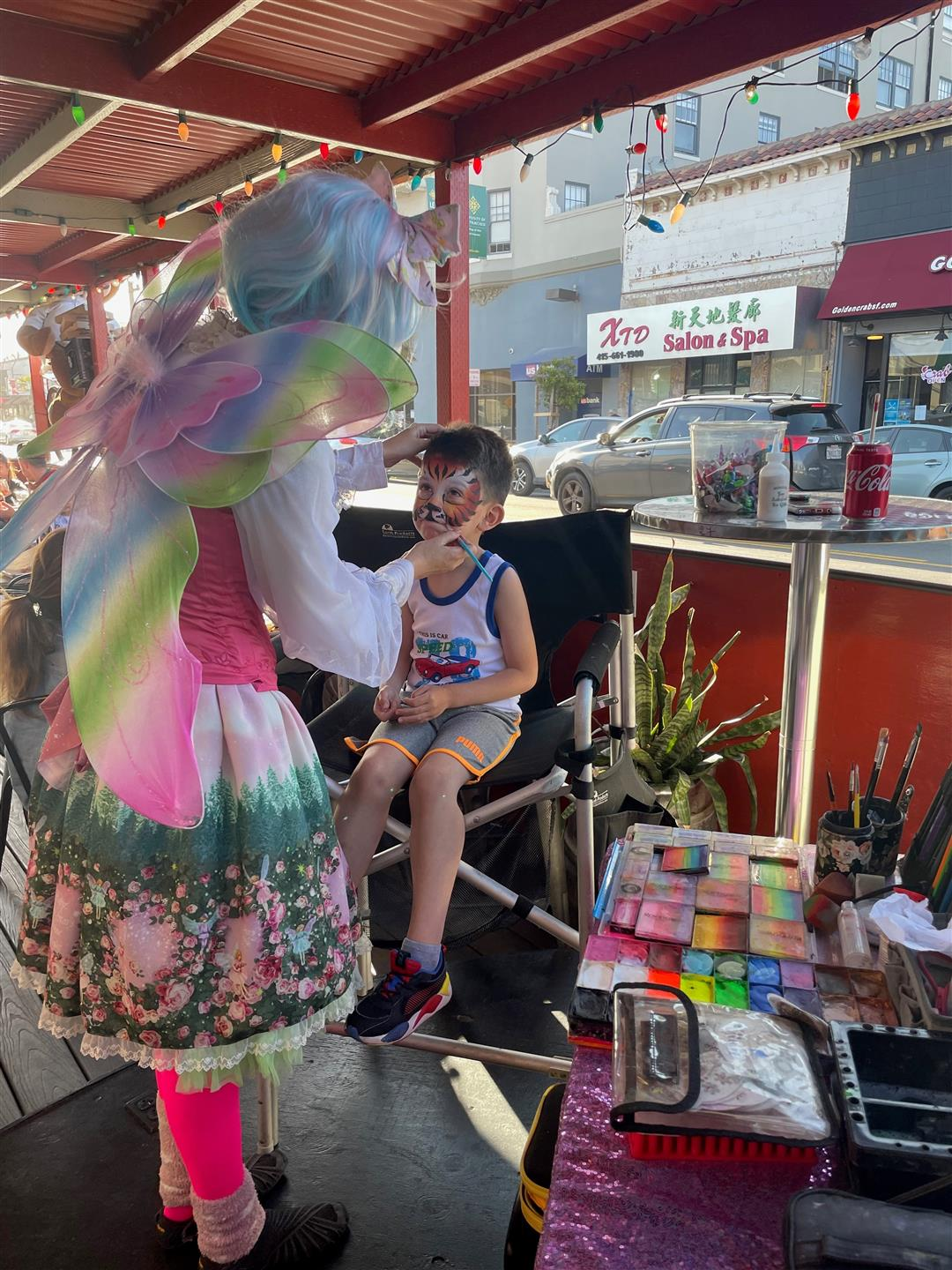 boy sitting down getting his face painted as a tiger from a woman dressed as a fairy