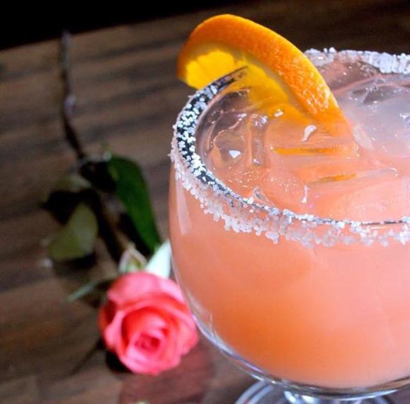 special flavored margarita on the rocks with a salted rim and an orange slice.