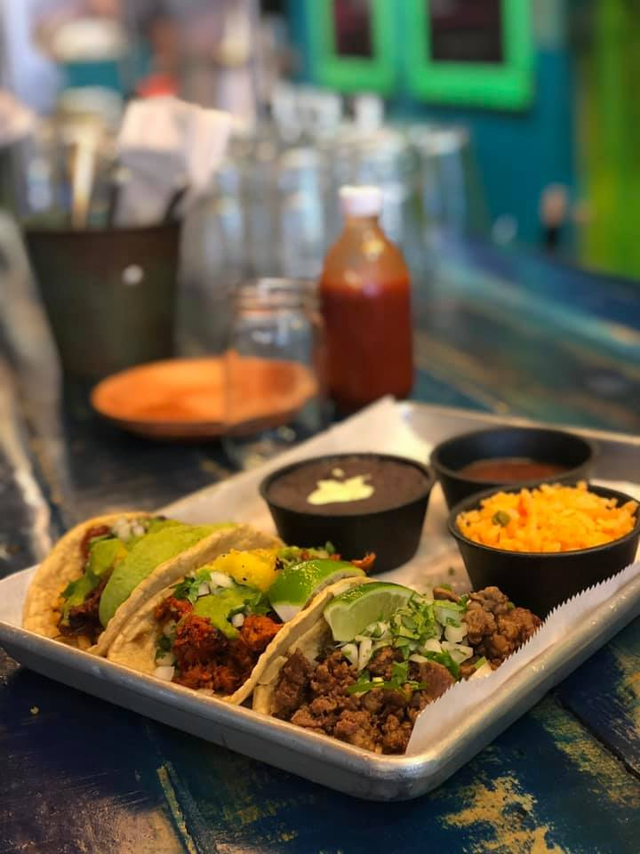 three tacos with sides on a tray
